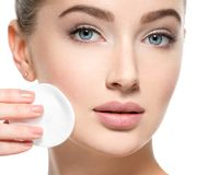 Girl removes makeup cotton ball from face Stock Photo
