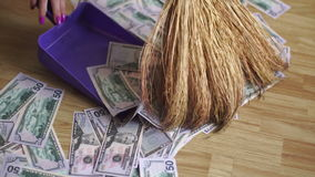 Girl removes money with the broom and dustpan stock footage