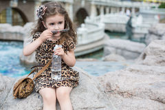 The girl removes sun glasses sitting on a rock. Next to a fountain stock photos