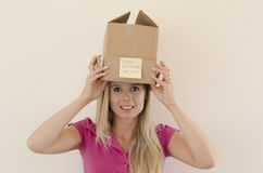 Girl removing the box from her head. Model removing the box with the sign Think outside the box on it from her head smiling royalty free stock photo