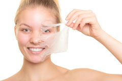Girl removing facial peel off mask. Beauty skin care cosmetics and health concept. Closeup young woman face, girl removing facial peel off mask isolated on white Royalty Free Stock Images