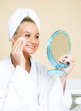 Girl removing makeup with a sponge Stock Photography