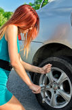 Girl removing a wheel Royalty Free Stock Photography