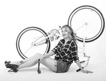 Girl repairing bike. Blonde girl with a bicycle in a retro style on a white background Stock Photo