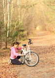 Girl repairing a bike between trees Stock Image