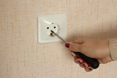 The girl is repairing an electrical outlet, close-up royalty free stock photo