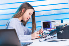 Girl repairing electronic device on  circuit board Stock Photos