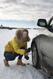 Girl repairing her car outside the city. Girl stopped on the road and your car repairs Royalty Free Stock Image