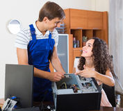 Girl and repairman fixing computer Stock Photos