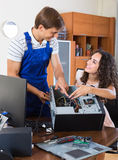 Girl and repairman fixing computer Royalty Free Stock Image