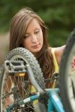 Girl repairs a bike Stock Images