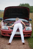 Girl repairs the car Stock Image