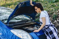 girl repairs car with an open hood on road stock photography