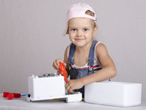 Girl repairs screwdriver toy microwave Royalty Free Stock Photography