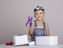 Girl repairs toy appliances Royalty Free Stock Image