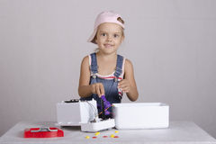 Girl repairs toy microwave Stock Photo
