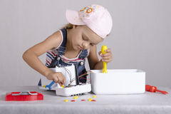 Girl repairs toy small home appliances Stock Images