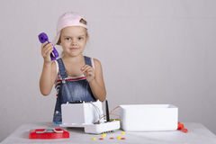 Girl repairs toy small home appliances Royalty Free Stock Images
