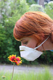 Girl in respirator smelling flower. Girl smelling flower through protective mask Royalty Free Stock Photo