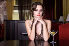 The girl at restaurant. The posing girl at restaurant in style old-fashioned. She drinks vine Stock Photos