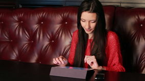 Girl in a restaurant with a tablet Royalty Free Stock Photo