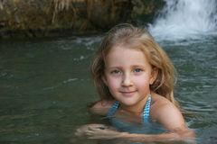 Girl resting. Baby girl by the waterfall Royalty Free Stock Image