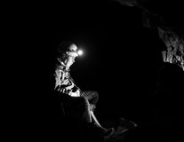Girl resting in an abandoned mine with light from head torch Stock Images