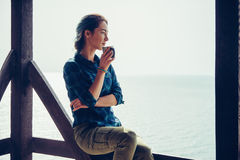 Girl resting in arbor on coast. Smiling young woman sitting with cup in wooden arbor and enjoying view of sea Royalty Free Stock Image