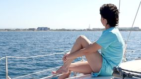 The girl is resting on board a yacht or boat on a sunny day on the open sea. A woman sits on the deck and looks into the. Distance. Recreation and tourism. Slow stock footage