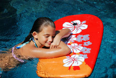 Girl Resting on a Boogie Board. A girl takes a break from boogie boarding in beautiful blue tropical waters royalty free stock images