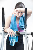 Girl resting after cardio workout. Young and beautiful girl with towel resting after treadmill work out holding a bottle with water Stock Image