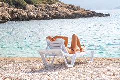 Girl resting in a deck chair and watching the sea. Tourism, recreation Royalty Free Stock Image