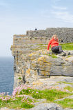 Girl resting in Dun Aengus, an ancient fort. Royalty Free Stock Photo