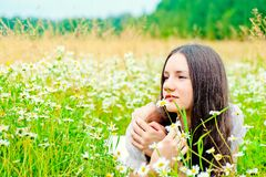Girl resting in a field of chamomile Stock Image