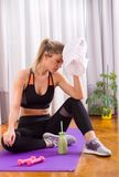 Girl resting on floor after workout. Pretty young girl wiping sweat from forehead after workout on yoga mat at home. Exercise and healthy lifestyle Stock Images