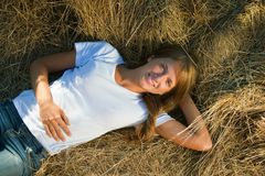 Girl resting on fresh straw Royalty Free Stock Photography