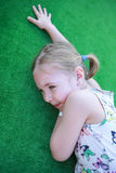 Girl resting on the green carpet. Childhood. Royalty Free Stock Image