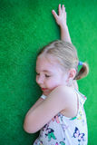 Girl resting on the green carpet. Sleep well. Royalty Free Stock Photo