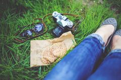 Girl resting on green grass with cookies and camera Stock Images