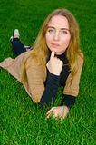 Girl resting on the green lawn Stock Image