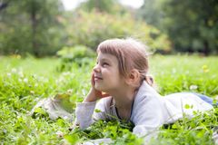 Girl    on   green meadow. Girl   resting on   green meadow in   summer park stock image