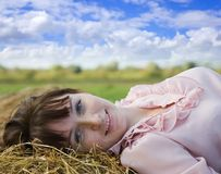 Girl resting on  hay Royalty Free Stock Images