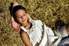Girl resting on a haystack Stock Images