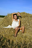 Girl resting on a haystack Royalty Free Stock Images