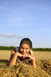 Girl resting on a haystack Royalty Free Stock Photos