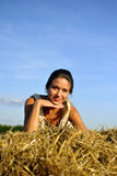 Girl resting on a haystack Stock Image