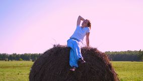 Girl resting on a haystack at sunset stock video