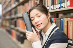 Girl resting head on old book Stock Images