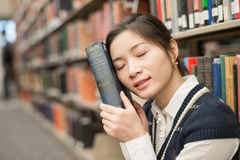 Girl resting head on old book Stock Photography