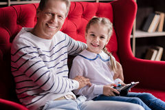 Girl resting with her grandfather and holding the game console Royalty Free Stock Images